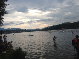Swimmers are headed out surrounded by kayaks.
